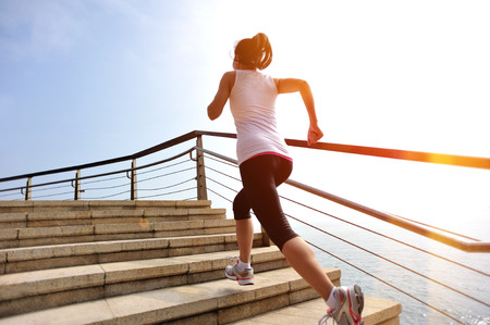 healthy lifestyle sports woman running on stone stairs seaside