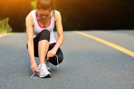shoelaces: young fitness woman tying shoelaces on road