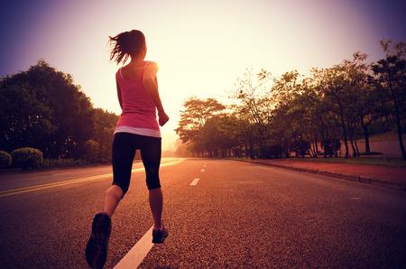 道路で走っている若いフィットネス女性。