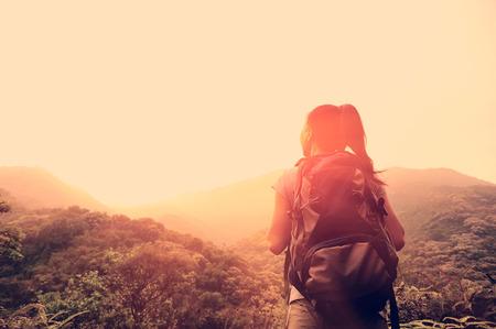 inspiración: Mujer senderismo disfrutar de la hermosa vista al pico de la monta�a