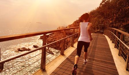 vida sana: Mujer deportes de estilo de vida saludable que se ejecuta en la playa pasarela de madera Foto de archivo