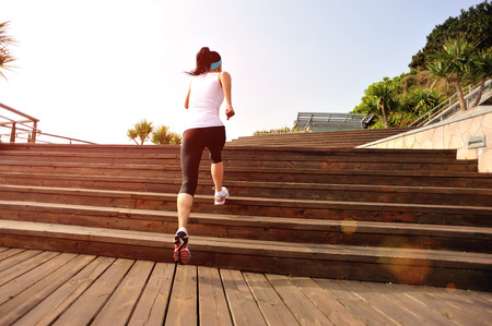 woman stairs: healthy lifestyle fitness sports woman running on wooden stairs