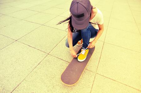 shoelace: young woman skateboarder tying shoelace