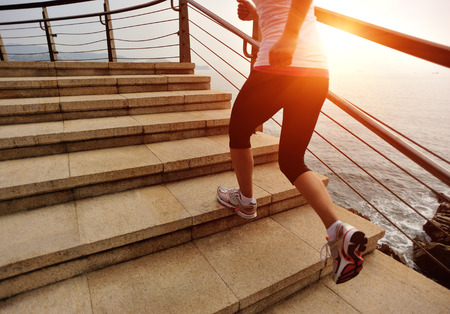 stone stairs: sports woman running on stone stairs seaside