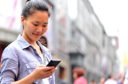 niñas chinas: hermosa mujer asiática joven con teléfono inteligente en la calle comercial Foto de archivo