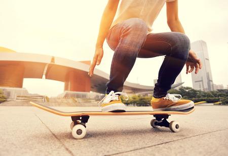skateboarder benen skateboarden truc ollie bij stad skatepark Stockfoto