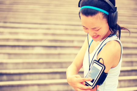 mp3 player: Runner athlete listening to music in headphones from smart phone mp3 player smart phone armband.woman fitness jogging workout wellness concept.
