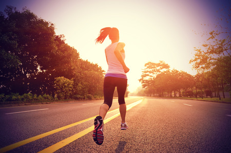 runners: Runner athlete running at road. woman fitness sunrise jogging workout wellness concept.