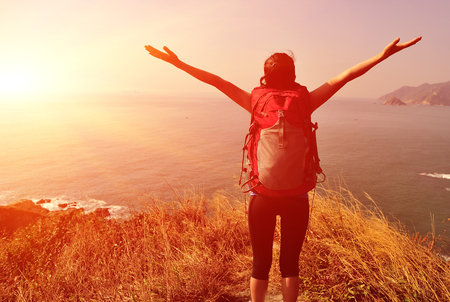 cheering hiking woman stand mountain peak looking at the view with arms open Stock Photo