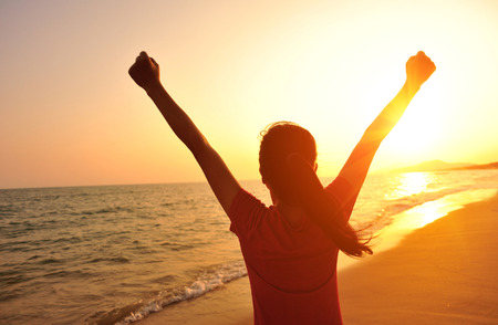 chinese people: cheering woman open arms at sunset seaside beach