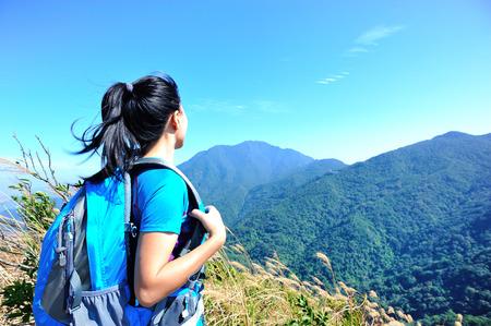 free image: Woman hiker stand at mountain peak.