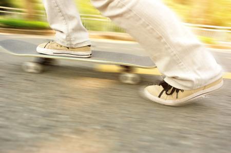 speeding: Speeding skateboarding woman legs on road.