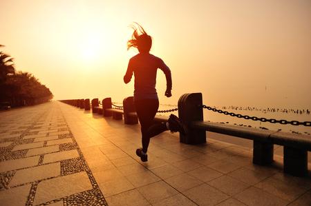 해변에서 실행하는 러너 선수. 여성 피트니스 실루엣 일출 조깅 운동 웰빙 개념. 스톡 콘텐츠