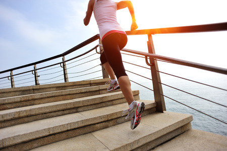 sports woman running on stone stairs seaside