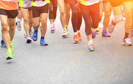 jog: Unidentified marathon athletes competing in fitness and healthy active lifestyle feet on road