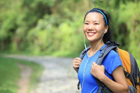 Hiking woman on forest trail Stock Photo