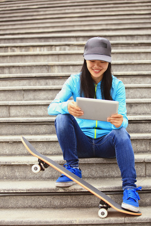 step well: woman skateboarder  sitting on stairs using digital tablet