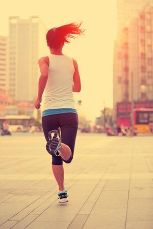 gente corriendo: Runner atleta que se ejecuta en calle de la ciudad. Aptitud de la mujer trotar entrenamiento concepto de bienestar.