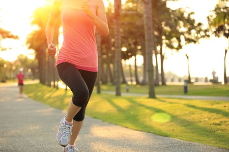 fit woman: runner athlete running at tropical park.