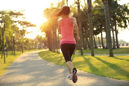 personas trotando: Runner atleta ejecuta en rastro parque tropical. mujer de fitness trotar entrenamiento concepto de bienestar. Foto de archivo