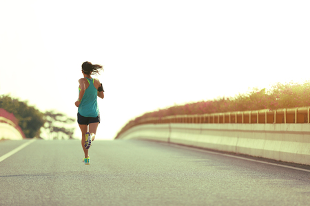 young woman runner running on city bridge road