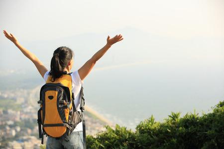niñas chinas: excursionista de joven brazos abiertos pico de la montaña Foto de archivo