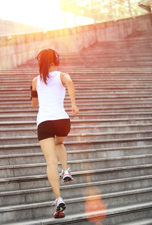 woman run: Runner athlete running on stairs  and listening  music