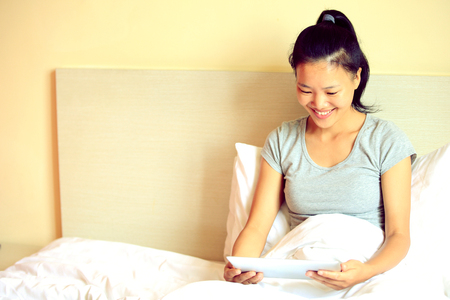 koreans: Young Asian woman using a tablet PC on a bed