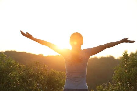 woman hiking: cheering woman open arms at sunrise mountain peak