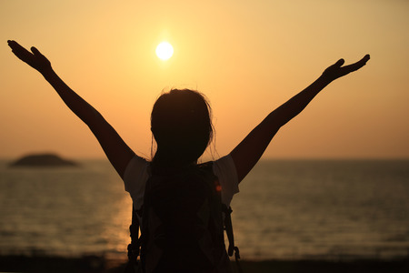 woman freedom: cheering hiking woman open arms to the sunrise stand at seaside mountain Stock Photo