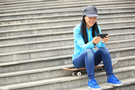 one teenager: woman skateboarder sit on stairs use her cellphone Stock Photo