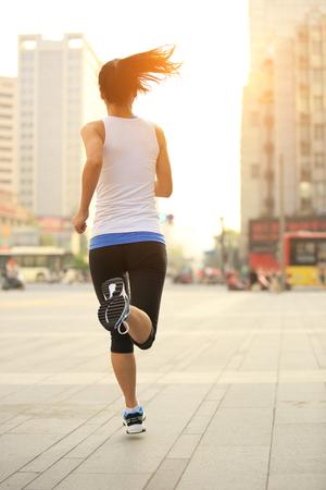 vida sana: Runner atleta que se ejecuta en calle de la ciudad. Aptitud de la mujer trotar entrenamiento concepto de bienestar.