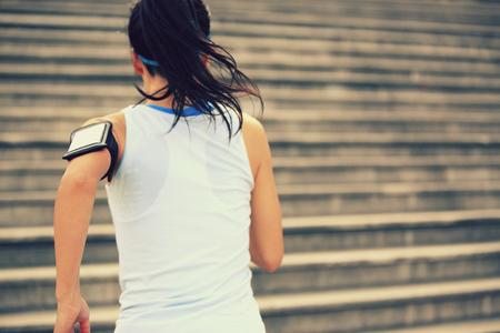 subiendo escaleras: Runner atleta que corre en las escaleras. Aptitud de la mujer trotar entrenamiento concepto de bienestar.