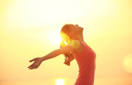 vrouw open armen onder de zonsopgang op zee