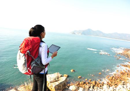 woman hiking: hiking woman  on seaside mountain rock and use digital tablet taking photo Stock Photo