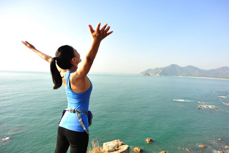 hiking woman stand seaside rock looking the view with arms open