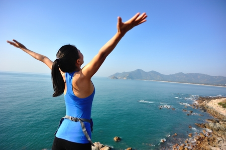 human arms: hiking woman stand seaside rock looking the view with arms open