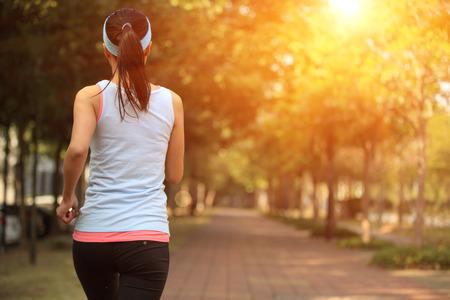 生活方式: 健康的生活方式女人在城市公園的路面上運行