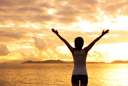 cheer: woman open arms under the sunrise at seaside Stock Photo