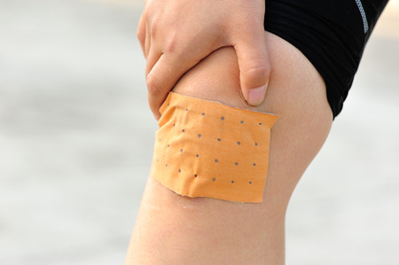 a wound: wound plast on sports injured knee Stock Photo