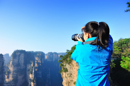taking photo: woman photographer taking photo at zhangjiajie national forest park, china