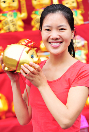traditional culture: young asian woman hold a golden piggy bank meaning wealthy in the traditional chinese culture