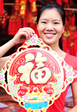 gung fu: young asian woman hold a red chinese character Fu. Fu meaning blessing, happiness