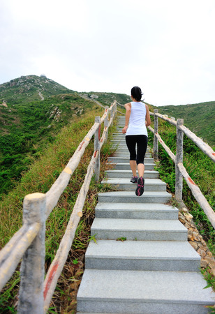 healthy girls: sports woman running on mountain stairs Stock Photo