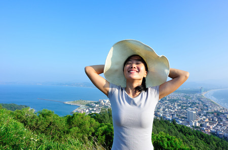 black hat: woman tourist happy seaside mountain peak