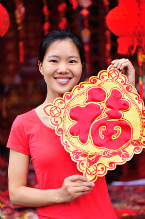 gung fu: young asian woman hold a red chinese character fu. fu meaning blessing, happiness Stock Photo