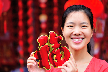 gung fu: young asian woman hold a red chinese characterfu. fu meaning blessing, happiness.