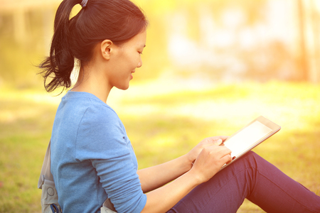 chinese woman: woman college student use tablet pc sit on grass Stock Photo