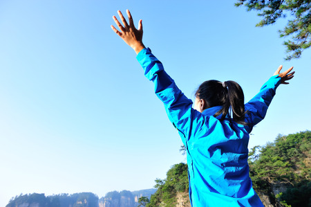 open arms: cheering woman open arms on mountain peak