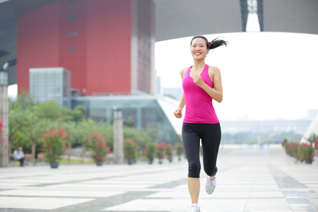 foot bridges: Young healthy asian woman jogging at city in the morning. Stock Photo